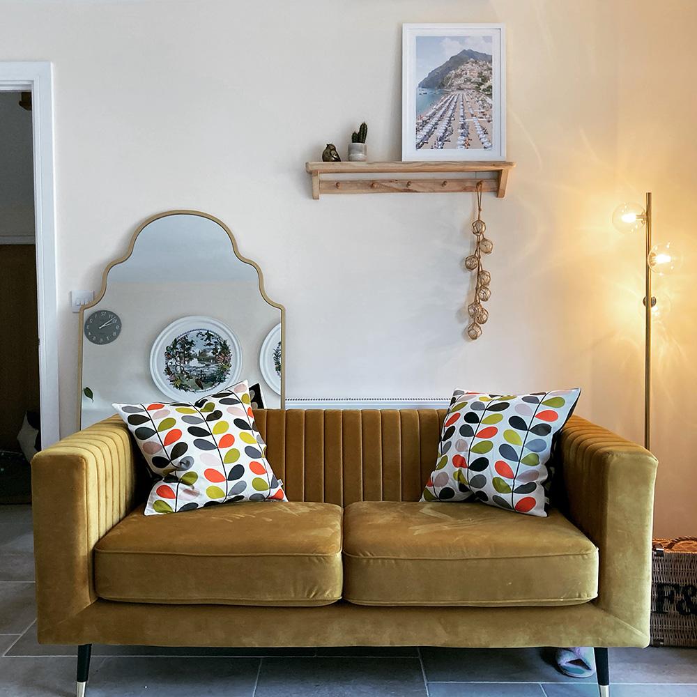 Senffarbenes Sofa im Raum mit goldenen Accessoires